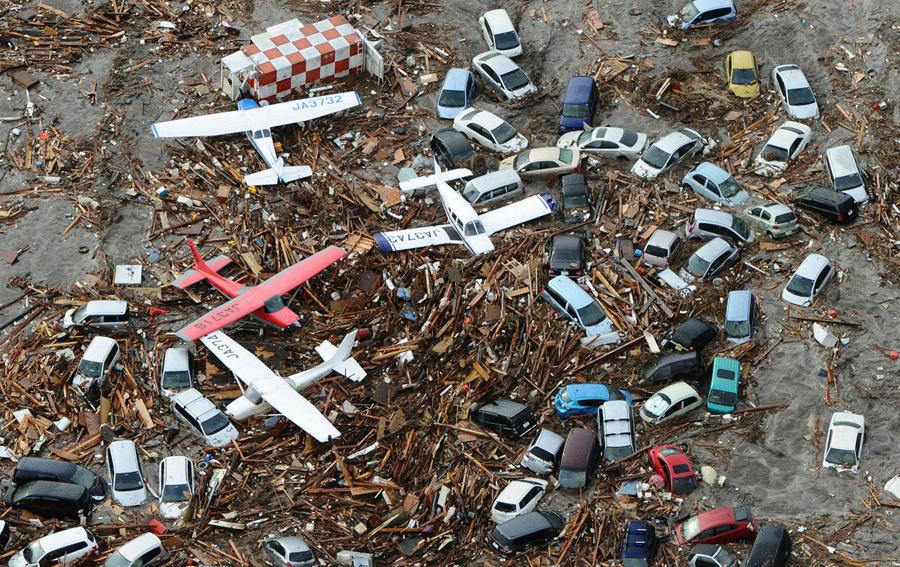 Автомобили и самолеты среди мусора в аэропорту Сендай, 11 марта 2011 года.
