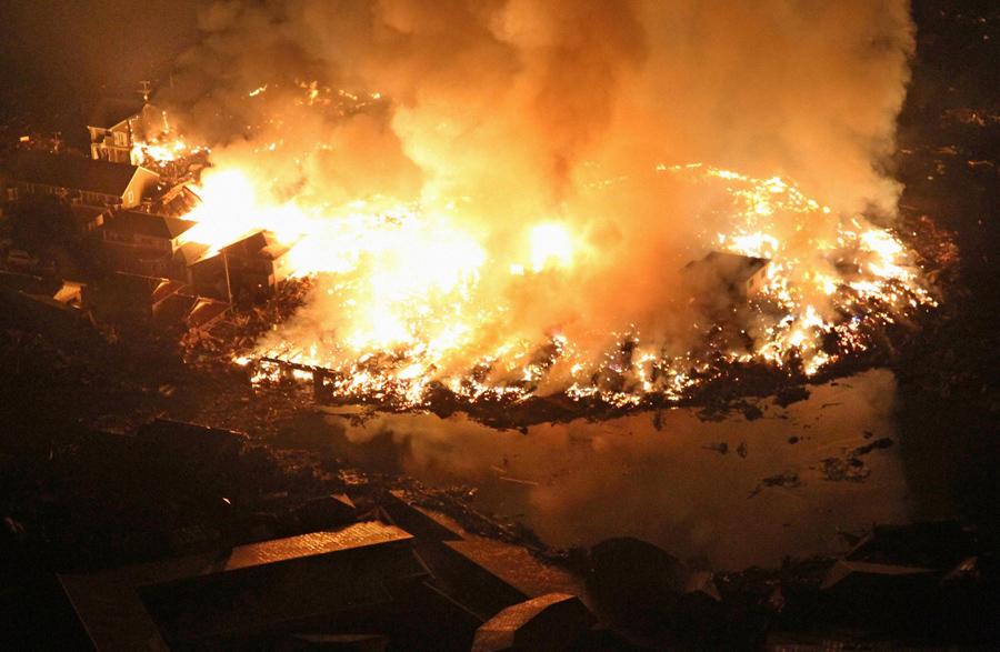 Горящие дома ночью, после землетрясения в городе Натори, 11 марта 2011 года.