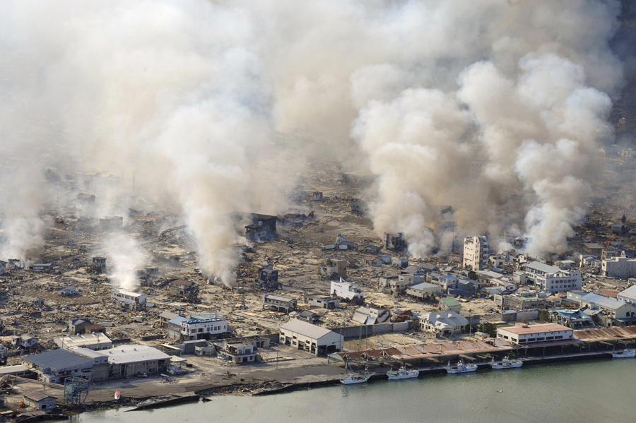 Дым поднимается в небо от горящих зданий в поселке Ямада префектуры Иватэ, 12 марта 2011, на следующий день после землетрясения и цунами.