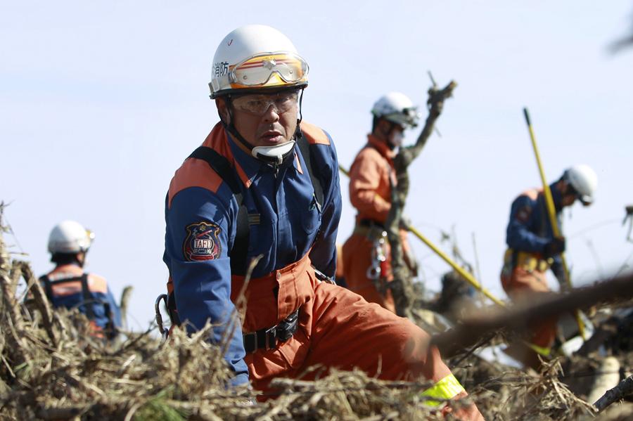 Пожарные в поисках людей, 14 марта 2011 года в Сома, префектура Фукусима, три дня после мощного землетрясения и цунами.