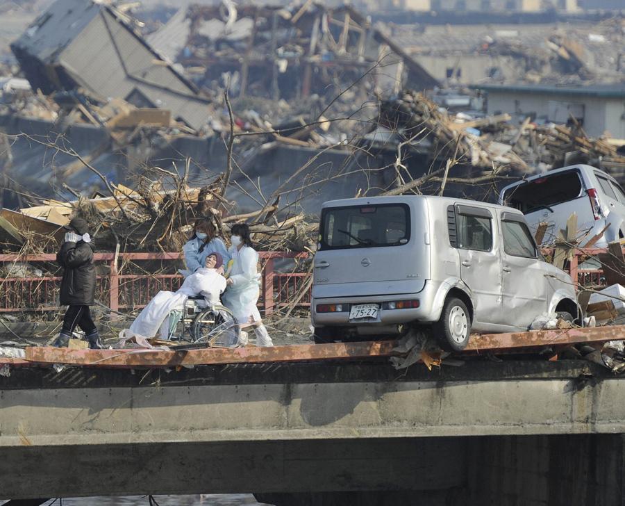 Женщину эвакуировали из разрушенной больницы в поселке Оцути, префектура Иватэ, 13 марта 2011 года.