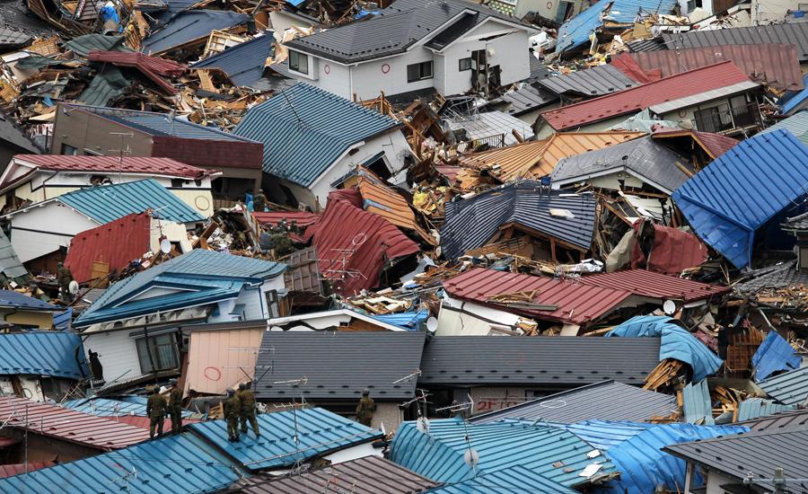 Спасатели ходят среди разрушенных домов и кораблей, все было уничтожено цунами в Мияко, 15 марта 2011 года.