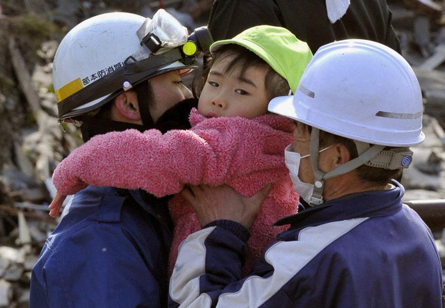 Спасатели эвакуируют девочку, которую они спасли из здания после землетрясения и цунами в Кесеннума, 12 марта 2011 года.