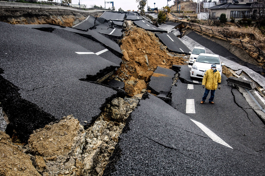 Мужчина ходит по разрушенной улице в разрушенном городе Исиномаки, 15 апреля 2011 года.