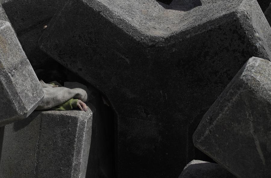 Рука человека погибшего в результате землетрясения и цунами, обнаружен среди бетонных плит, 14 марта 2011 года, в Тояма, Северная Япония.
