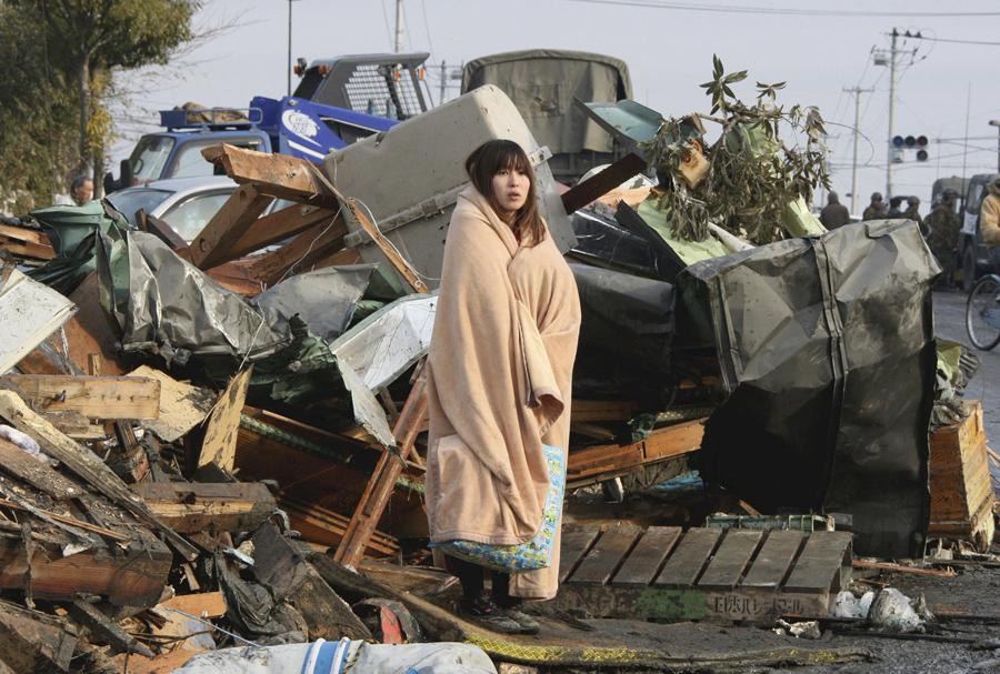 Женщина смотрит на разрушения вызванные цунами и землетрясение в городе Исиномаки, префектура Мияги, 13 марта 2011.