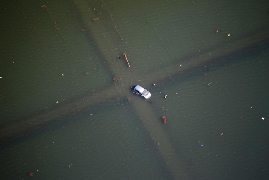 Полузатопленный автомобиль на перекрестке после землетрясения и цунами в Сендае, 12 марта 2011.