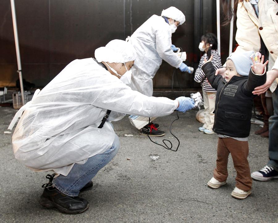 Люди в защитных снаряжения проверяют детей на признаки радиации в эвакуационной зоне рядом с Фукусимой, 13 марта 2011.
