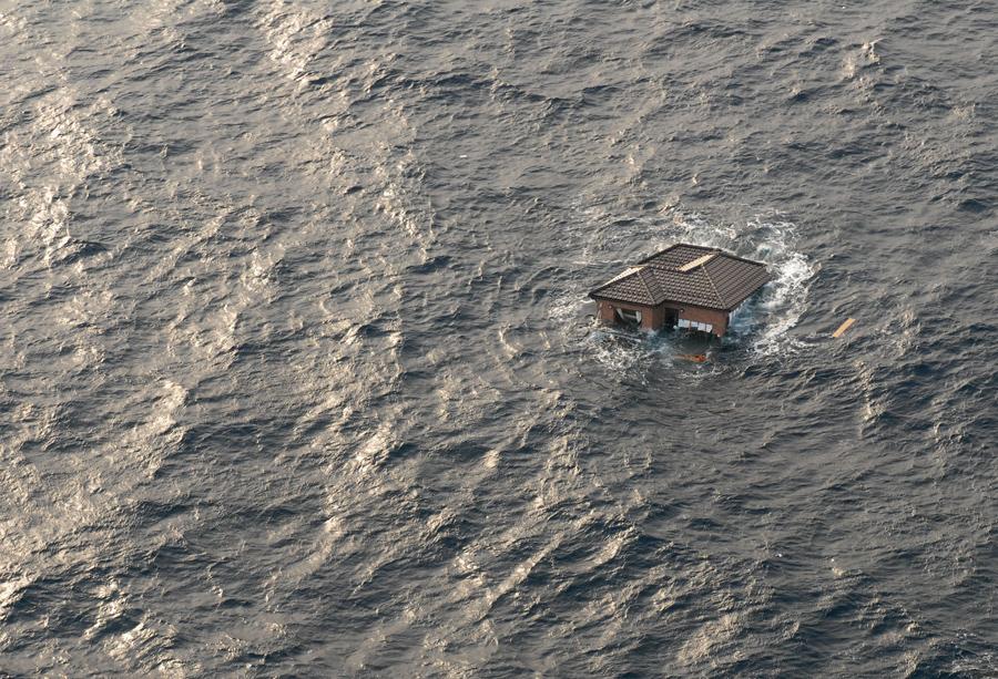 Японский дом плавает в Тихом океане, 13 марта 2011 года. В прибрежных водах возле г. Сендай, Япония.