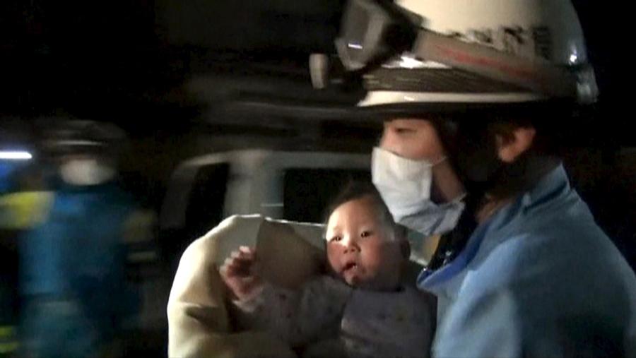 Спасение грудного ребенка из развалившегося дома, вызванного землетрясением в городе Машику, префектура Кумамото, на юге Японии, 15 апреля 2016 года.