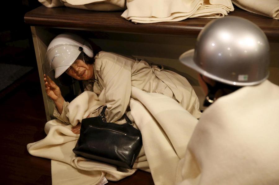Женщина прячется после очередного землетрясения, произошедшего в районе отеля в Кумамото, на юге Японии, 16 апреля 2016 года.