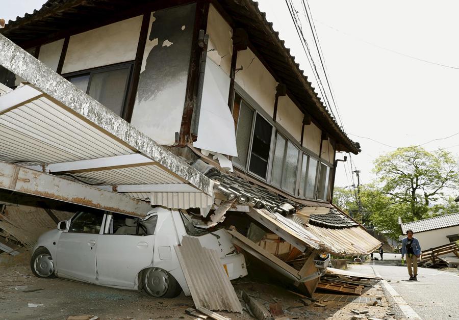 Мужчина проходит возле дома который рухнул на автомобиль в результате землетрясения, 15 апреля 2016 года.