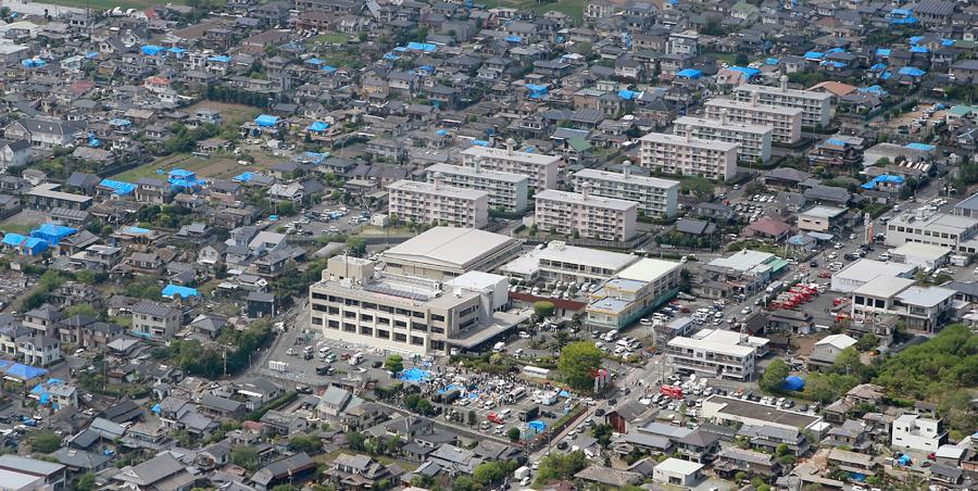 Вид с воздуха показывает город Машику. Поврежденные жилые дома покрыты голубым навесом для защиты их от дождя после землетрясения, 16 апреля 2016 года.