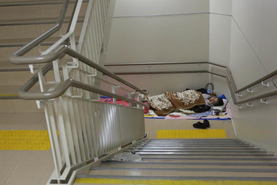 Местный житель спит в мэрии Кумамото после эвакуации их домов 17 апреля 2016 года в Кумамото, Япония.