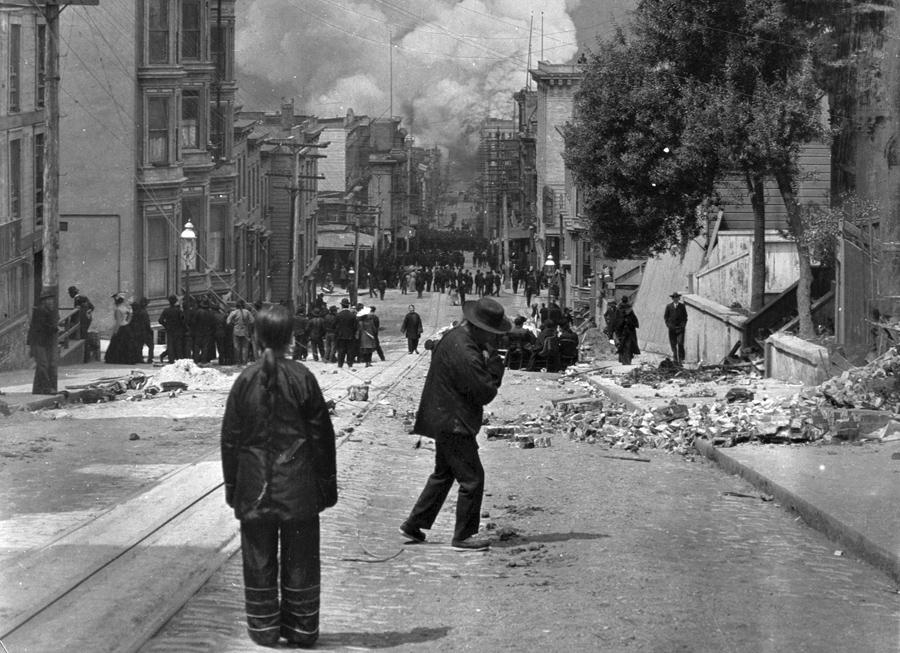 Жители Сан-Франциско стоят на улице в руинах, наблюдая за пожаром после землетрясения 18 апреля 1906 года.