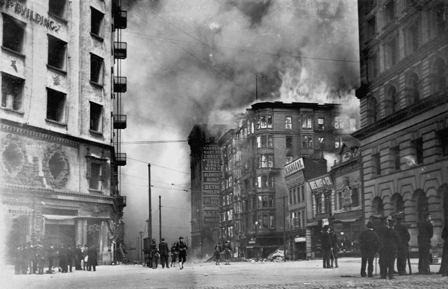 Люди смотрят как горит отель Винчестер после землетрясения 1906 в Сан-Франциско.