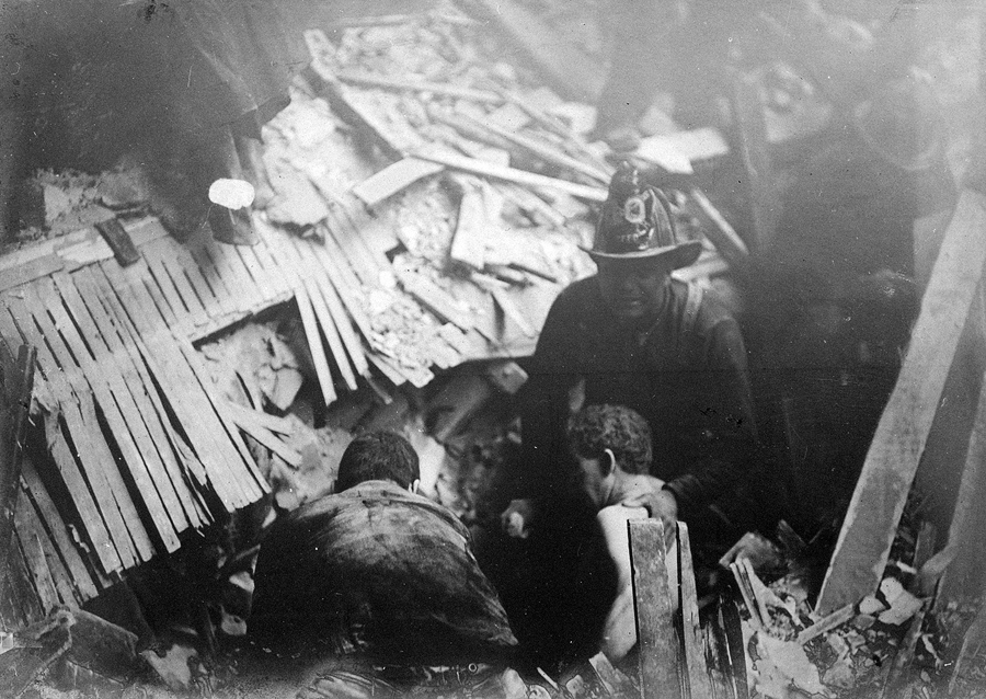 Спасатели вытаскивают выживших из под завалов.
