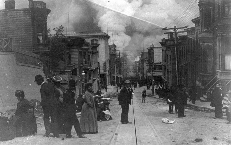 Несколько афро-американских семей на улице во время пожара в Сан-Франциско 1906 года, с облаками дыма вздымающиеся на горизонте.