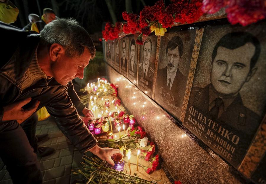 Мужчина зажигает свечи у мемориала посвященного пожарным и работникам станции, которые погибли после катастрофы на Чернобыльской АЭС во время ночной службы, 25 апреля 2015 года.