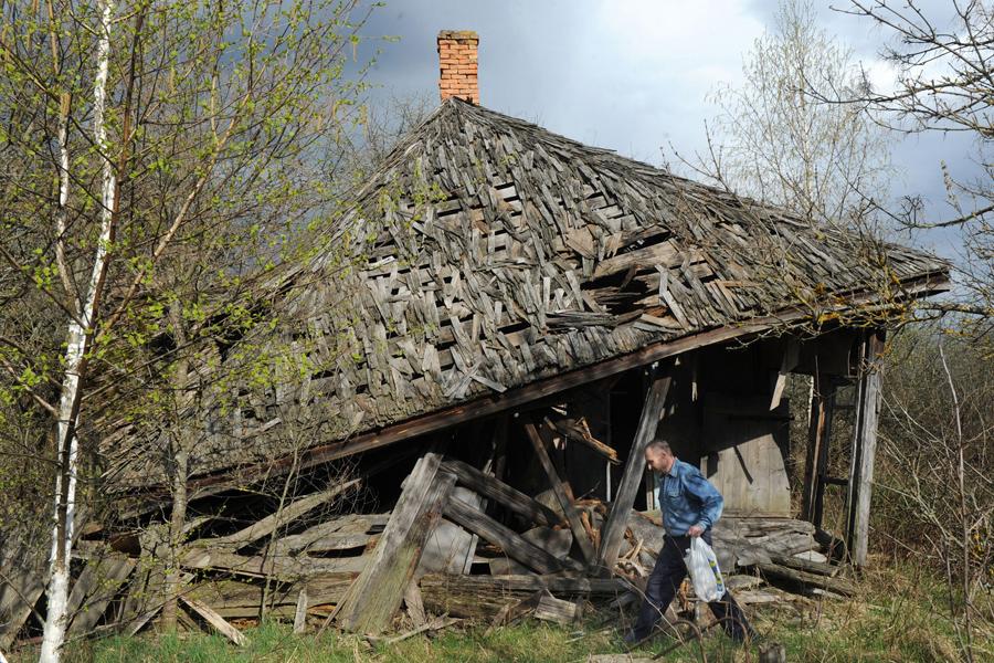 Мужчина проходит мимо разрушенного дома в заброшенной деревне Вяжище, Беларусь, 23 апреля 2011 года.