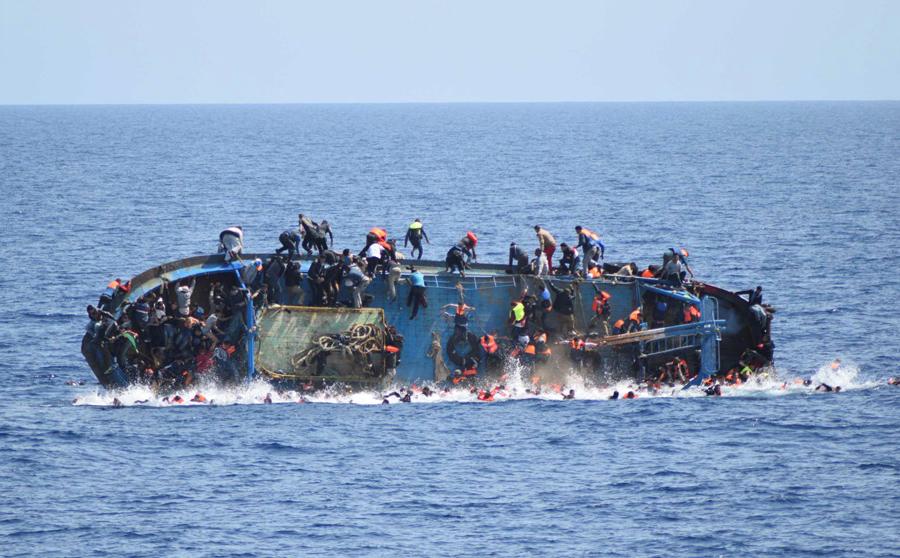 Опрокидывающаяся лодка с мигрантами у берегов Ливии, 25 мая 2016 года.