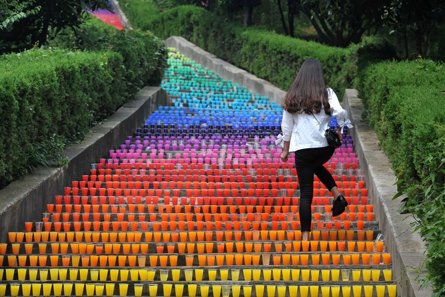 Женщина поднимается по выстроенным пластиковым стаканчикам, арт-проект четырех студентов колледжа, в городе Ухань, провинция Хубэй, Китай, 24 мая 2016.