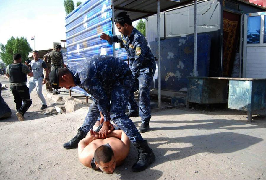 Иракский полицейский Саад Али Табита задерживает горе-смертника на контрольно-пропускном пункте к северу от Багдада, 25 мая 2016 года.