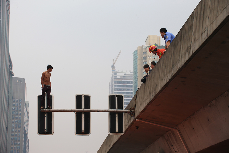 Человек стоит на опоре светофоров он угрожает спрыгнуть, 24 мая 2016 года, в городе Чанша, провинции Хунань, Китай. Сотрудников полиции и  работники пожарной и дорожной полиции установили надувной матрас снизу, но человек упал мимо него, после попытки запрыгнуть на эстакаду. Скорая помощь отправила мужчина в ближайшую больницу. Причины его действий неизвестны.