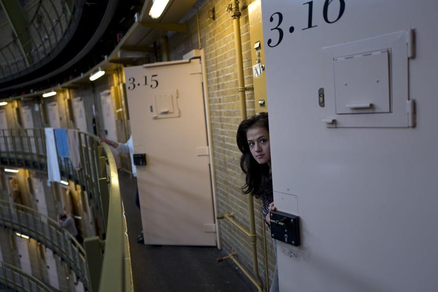 Беженка из Афганистана Шазия Лютфи, выглядывает через дверь своей комнаты в бывшей тюрьме в de Koepel в Харлеме, Нидерланды, 7 мая 2016 года. Правительство Нидерландов, Бельгии и Норвегии помещают в закрытые тюрьмы.