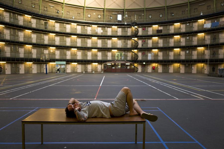 Иранский мигрант Эхсан, 25 лет, лежит на столе в бывшей тюрьме De Koepel в Харлеме, Нидерланды, 6 мая 2016 года.