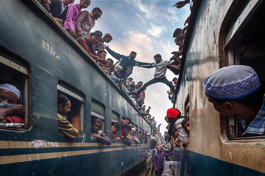 Молодые люди веселятся на крыше поезда. Там было слишком многие люди спешат домой после Bishwa Ijtema на железнодорожный вокзал Силхет, Бангладеш.