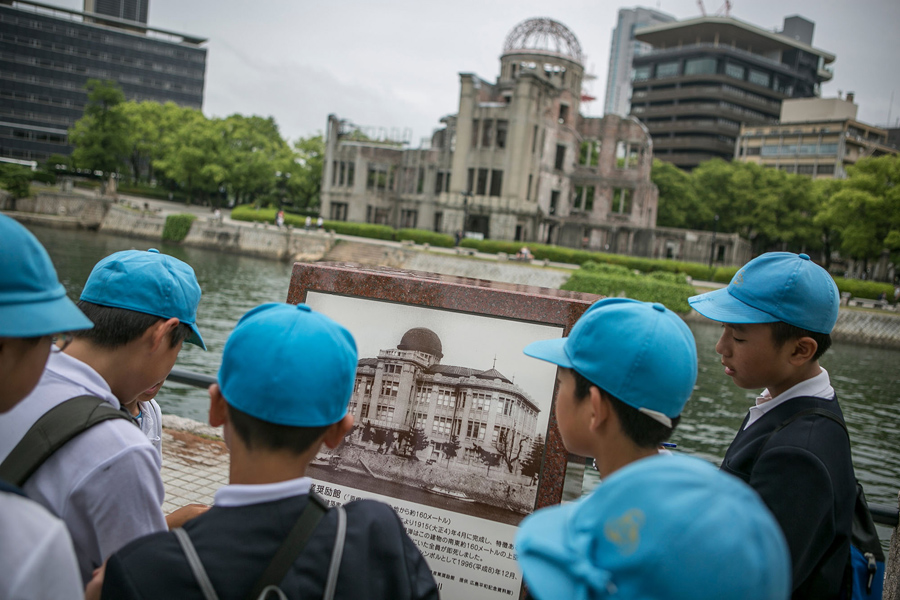 26 мая 2016 года, школьники смотрят на старую фотографию купола выставочного центра до взрыва атомной бомбы в Хиросиме, Япония.