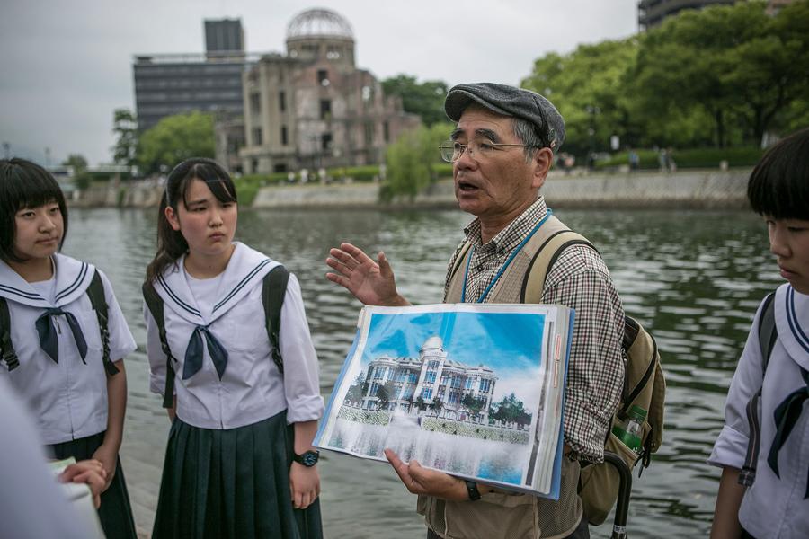 Руководитель группы выживших показывает для учащихся средних школ фотографию купола выставочного центра до атомной бомбардировки, 26 мая 2016 года.