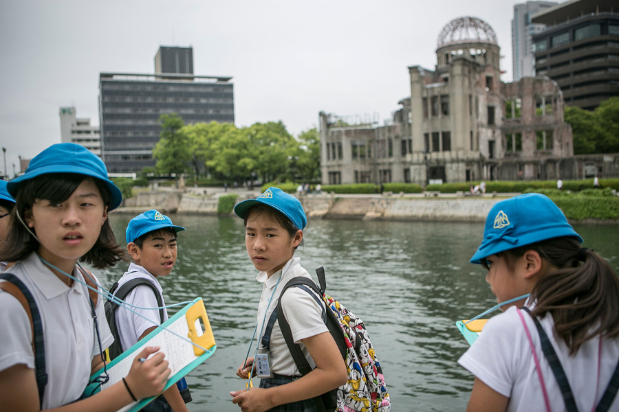 Школьники делают пометки и слушают гида, на месте разрушенного купола после падения атомной бомбы, 26 мая 2016 года в Хиросиме, Япония.
