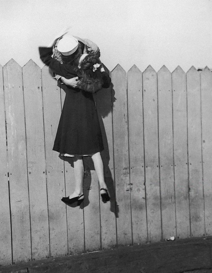 Моряк целует подругу наклоняясь через забор, 1945