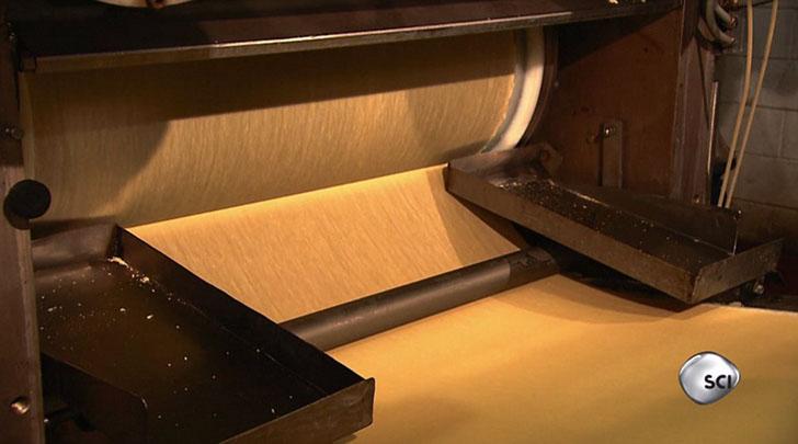 На ленте сильное давление в четыре тонны для того что бы спрессовать картофельные хлопья в лист, который позже будет разрезан.