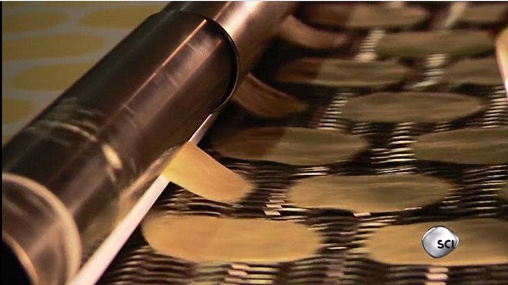 Чипсы с ленты подаются в форму, где они становятся идеально ровными.