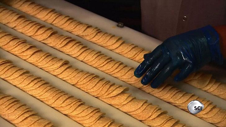 Работники завода проверяет чипсы вручную, после чего другой конвейер встряхивает и взвешивает их для пакования.