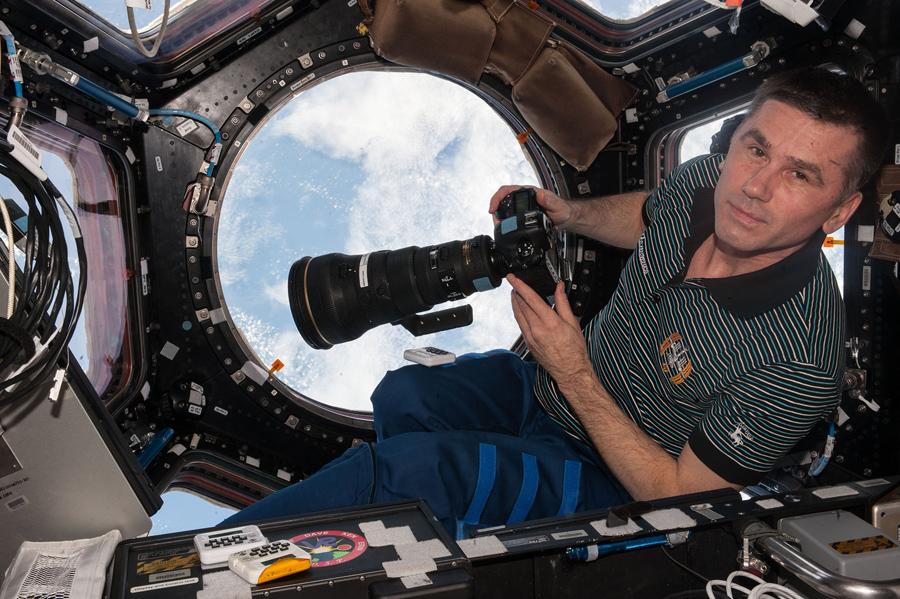 Бортинженер экспедиции Юрий Маленченко из Роскосмоса, в модуле МКС готовится сфотографировать землю с помощью 400 мм объектива.