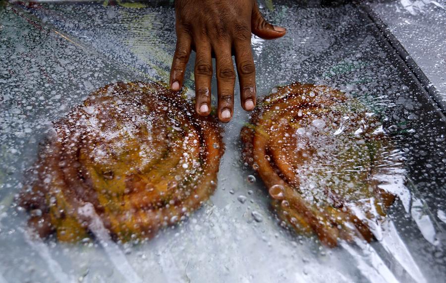 Еду накрывают полиэтиленовой пленкой, чтобы сохранить её от дождя во время священного месяца в первый день Рамадана, Дакка, Бангладеш, 7 июня 2016 года.