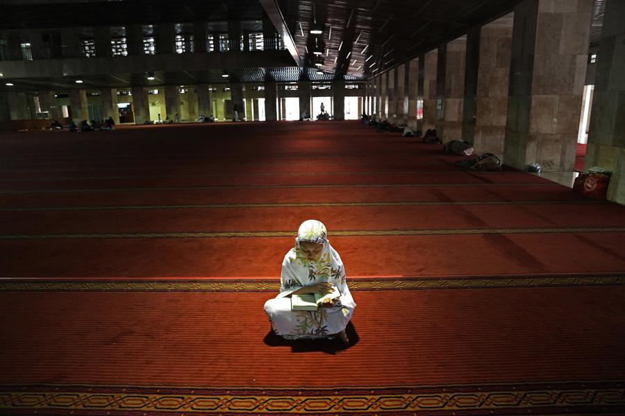 Мусульманка читает Коран в полдень после молитвы, первый день Рамадана в мечети Истикляль что в Джакарте, Индонезия, 6 июня 2016 года.