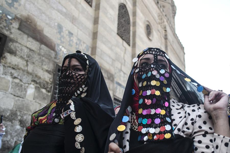 Египетские женщины, одетые в традиционную одежду прогуливаются по улице Аль-Мес во время празднования преддверии священного для мусульман месяца Рамадан в старом Каире, 2 июня 2016 года.