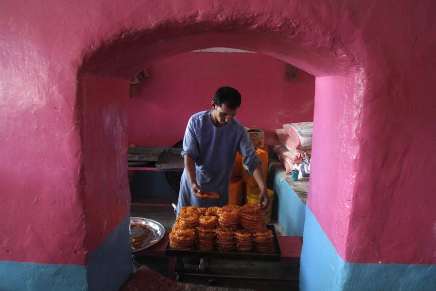 Мужчина из Афганистана делает сладости во время Священного месяца Рамадан в Кандагаре, Афганистан, 7 июня 2016 года.
