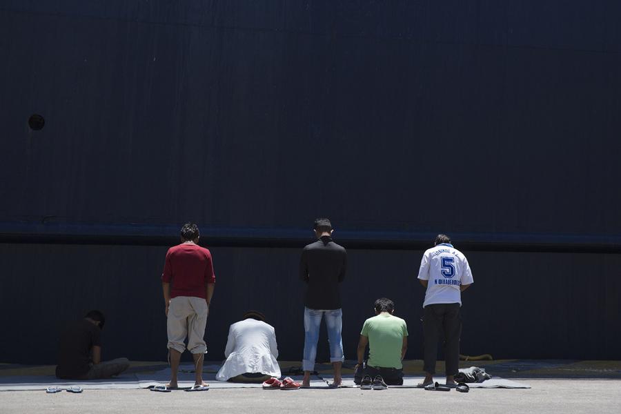Афганские мигранты в Греции молятся перед пришвартовавшимся паромом в порту Пирей, недалеко от Афин, 6 июня 2016 года.