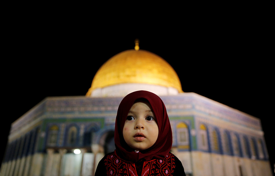 Девочка из Палестины молится перед куполом здания, 7 июня 2016 года.