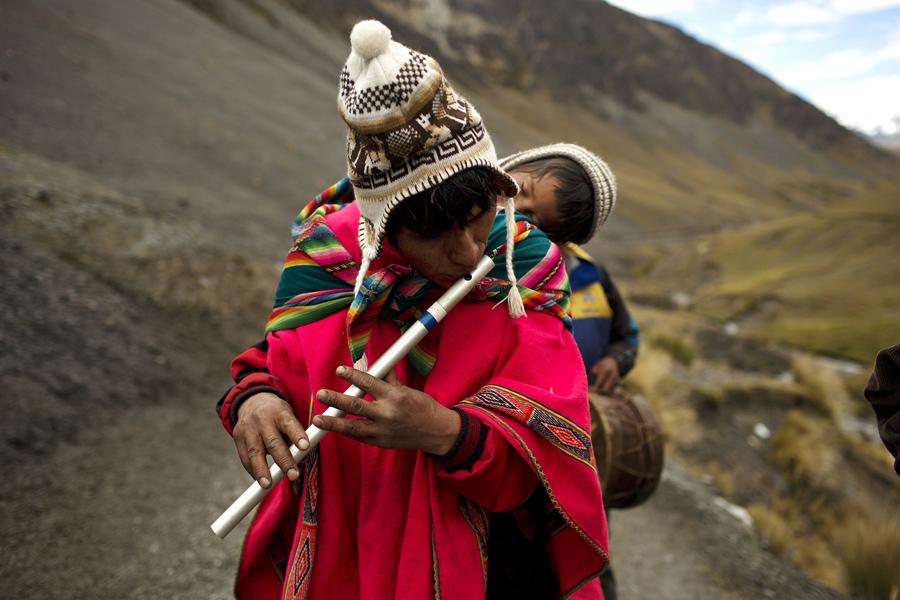 Мужчина со своим сыном играет на традиционной Андской флейте.