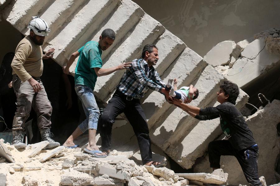 Сирийские добровольцы гражданской обороны и спасатели извлекают ребенка из-под обломков разрушенного здания, после авиаударов недалеко от Аль-калаша, в Северном сирийском городе Алеппо, 28 апреля 2016 года.