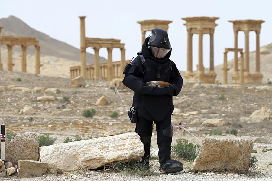 Российский военнослужащий ищет мины в развалинах Пальмиры, в Сирии.