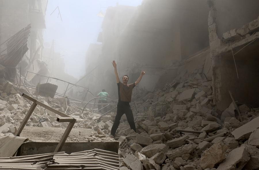 Мужчина жестикулирует у разрушенных зданий после авиаударов на удерживаемых повстанцами районе Аль-Калаша, в Северном сирийском городе Алеппо, 28 апреля 2016 года.