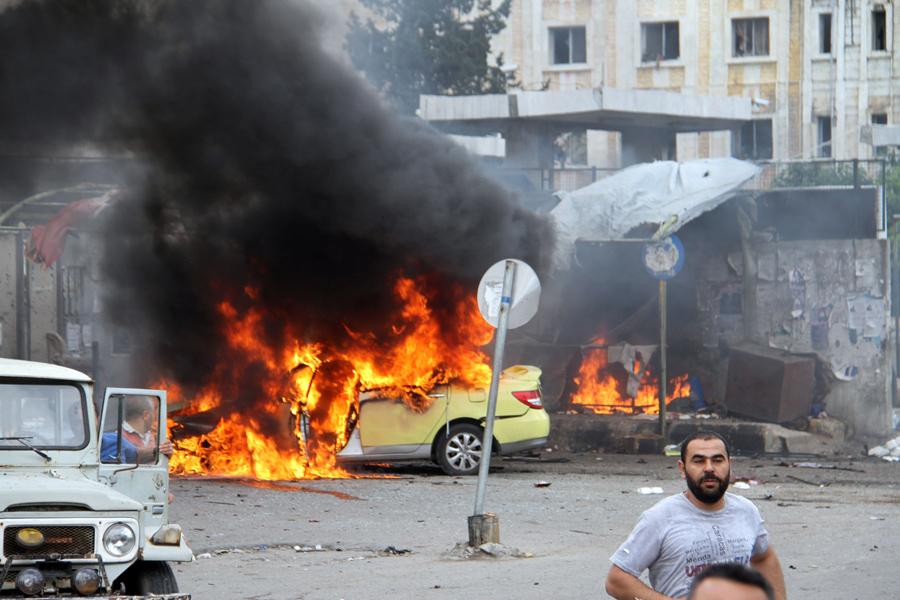 Сирийцы собрались перед горящей машины на месте, где смертники взорвали себя, в прибрежном городе Тартус, Сирия, 23 мая 2016 года.
